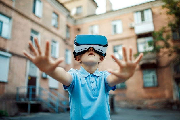 Faszinierter kleiner junge, der schutzbrillen der virtuellen realität vr verwendet. draussen
