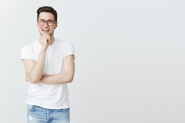 Faszinierter kluger junger mann in der brille, die gute idee hört