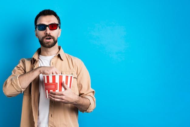 Faszinierter mann mit popcorneimer