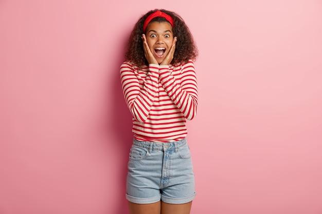 Fasziniertes glückliches junges mädchen mit dem lockigen haar, das im gestreiften roten pullover aufwirft