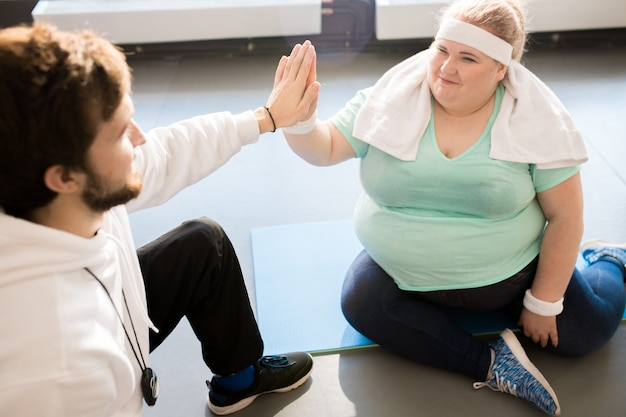 Fat woman high five mit trainer