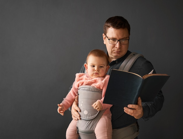 Fathre und sein kind in der babytrage an der grauen hintergrundwand, baby, das in der elternschaft trägt