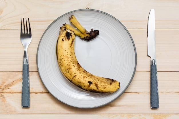 Faule banane auf einem teller auf einem hölzernen hintergrund