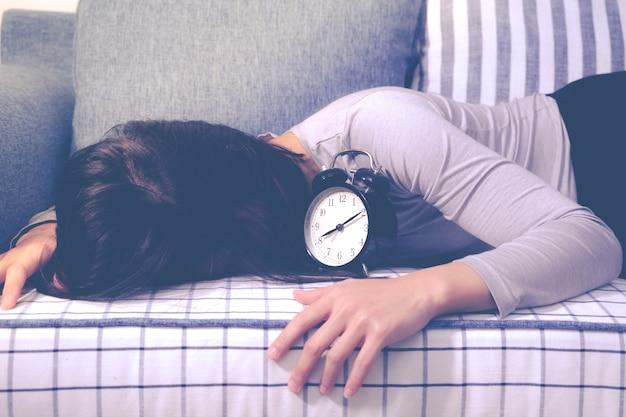 Faule frauen, die auf sofa nach der uhralarm, spätes weckkonzept niederlegen