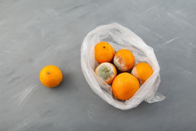 Faule verdorbene mandarinen oder orangen in plastiktüte auf grau