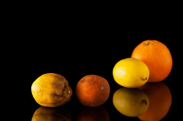 Faule zitrone und verdorbene orange auf einem verschwommenen hintergrund von frischen zitrusfrüchten.