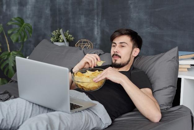 Fauler junger bärtiger mann, der auf bett liegt und chips isst, während film während der coronavirus-quarantäne auf laptop betrachtet