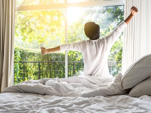 Fauler mann, der morgens in den steigenden händen des betts morgens mit frischem gefühl glücklich aufwacht