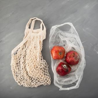 Fauler verwöhnter granatapfel mit schimmel in einweg-plastiktüte