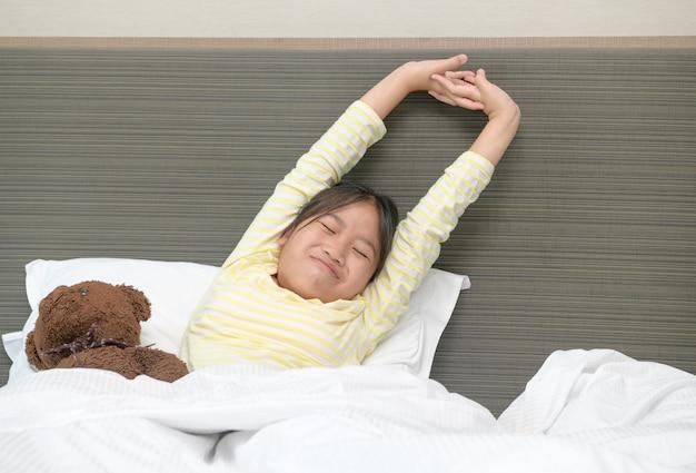 Faules kleines mädchen wacht auf und streckt sich am morgen auf dem bett, gesundheitswesen und guten morgen weltkonzept