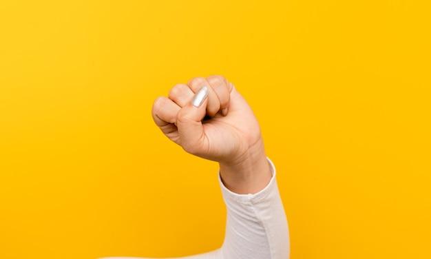 Faust eines mädchens mit dem herzen, mit allem zu kämpfen. selbstvertrauen entschlossenheit und entschlossenheit hände und gelber hintergrund