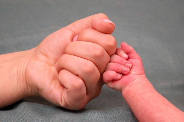 Fausthand des neugeborenen und faust der eltern zusammen