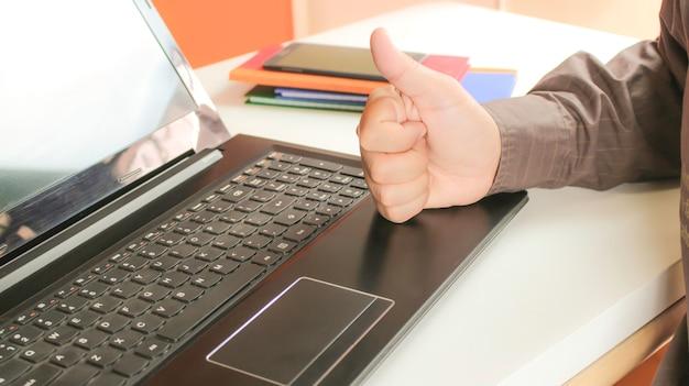 Fausthand mit laptop für gute geschäftsarbeit