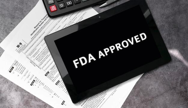 Fda-zulassung auf einem schwarzen tablet sowie mit steuerformularen und taschenrechner