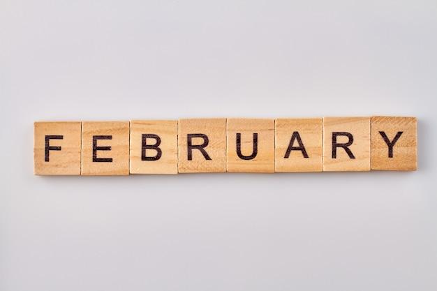 Februar wort geschrieben auf holzklötzen. auf weißem hintergrund isoliert.