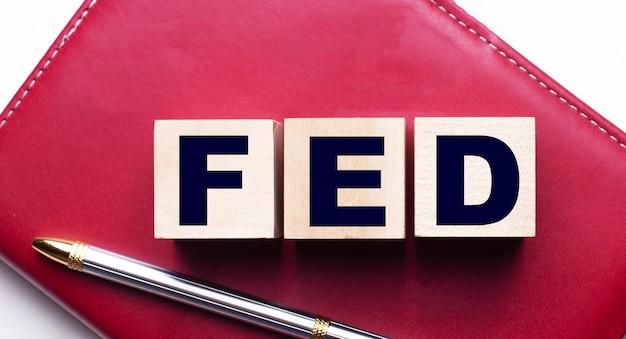 Fed besteht aus holzwürfeln, die auf einem burgunderfarbenen notizbuch in der nähe des stifts stehen