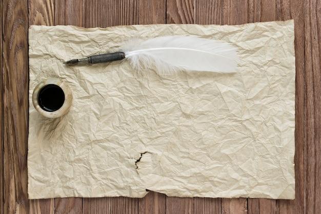 Feder mit tintenfass auf vintage-papierhintergrund und holztisch