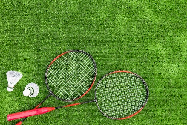 Federbälle mit rotem badminton auf grünem rasenhintergrund