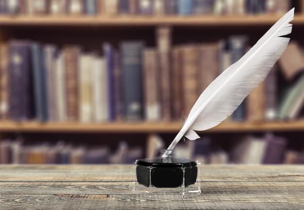 Federkiel und glastintenfass auf bibliothekshintergrund