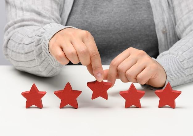 Feedback-konzept für die kundenerfahrung. fünf rote sterne, die beste bewertung für exzellente leistungen mit weiblicher hand zu treffen. weißer tisch
