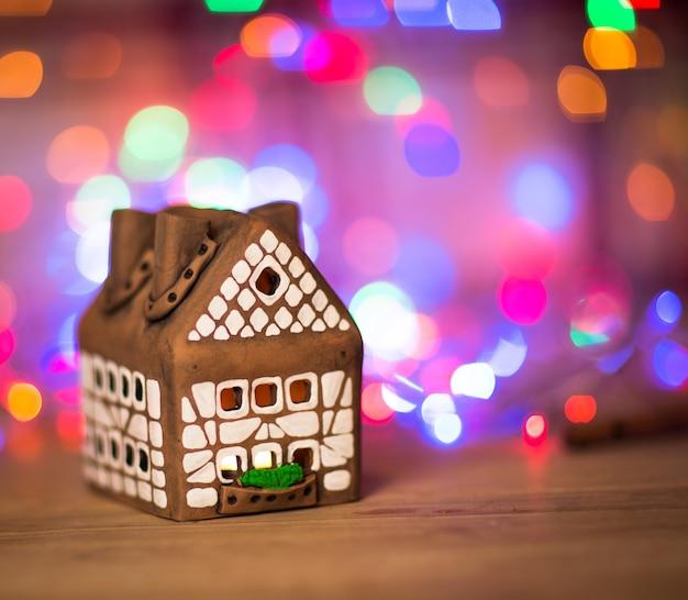 Feenweihnachtshauskuchen mit kerzenlicht innen, schmaler schärfentiefe und hintergrundlichtern