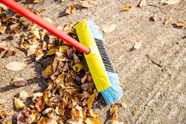 Fegen der abgefallenen blätter vom gartenboden zum recycling während der herbstsaison.