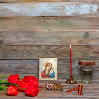 Feier der tag des sieges medaillen, orthodoxe ikone und brennende rote kerze, blumenstrauß aus roten tulpen und ein glas wodka mit stück roggenbrot