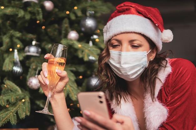 Feier des neuen jahres und weihnachten auf der distanz des konzepts. eine junge frau in einem weihnachtsmann-anzug und -hut hält ein smartphone vor dem hintergrund eines verzierten tannenbaums.