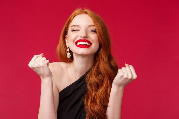 Feier, emotionen und schönheitskonzept. nahaufnahmeporträt der glücklichen herrlichen jungen rothaarigen frau im abendlichen schwarzen kleid, im roten lipgloss, tun meistertanz, triumphierend und lächelnd zufrieden