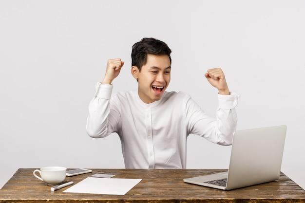 Feier, erfolg und finanzkonzept. netter junger asiatischer mann, der, geballte fäuste im hurra anhebend, ja geste, sitzender schreibtisch sich freut und schauen laptopschirm