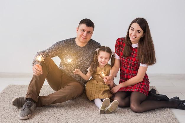 Feier, familie, neujahr, weihnachten und feiertagskonzept - glückliche eltern und kleine tochter