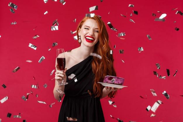 Feier, feiertage und partykonzept. porträt der sorglosen schönen jungen rothaarigen frau, die spaß am geburtstag hat, lachend feiert, während konfetti herumfliegen, glas champagner und kuchen halten