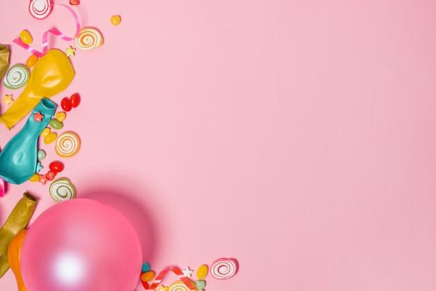 Feier flach legen. süßigkeiten mit bunten partyartikeln auf rosa hintergrund.