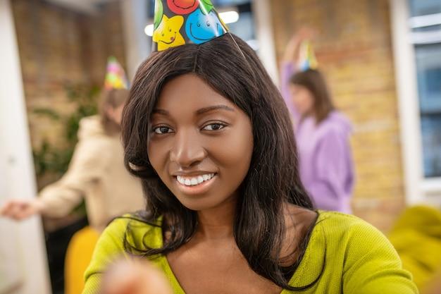 Feier, freude. junges langhaariges amerikanisches mädchen mit zahnigem lächeln, das partyhut und freunde trägt, die spaß hinter drinnen haben