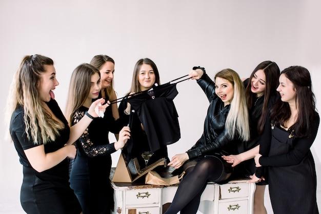 Feier, freunde, junggeselle, geburtstagsfeier und feiertagskonzept - glückliche frauen in den schwarzen kleidern mit den trinkgläsern, die dem geburtstagskind geschenke geben