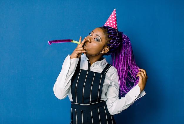 Feier, freunde, junggesellenabschied, geburtstagskonzept - lächelnde afroamerikanerin, die rosa parteihut trägt und gunsthorn bläst