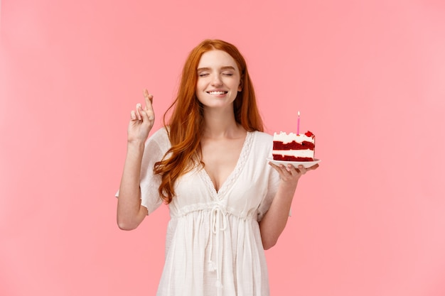 Feier, glückskonzept. attraktives verträumtes rothaariges mädchen im reizenden weißen kleid, b-day-kuchen haltend, kreuzfinger viel glück, bisslippe verführerisch schließen augen und wunsch, kerze zu blasen
