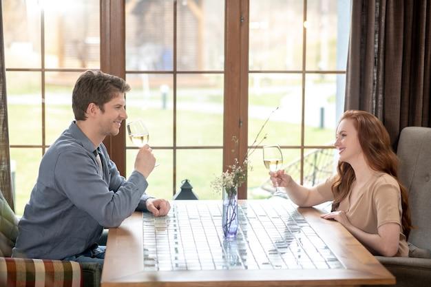 Feier. junger erwachsener fröhlicher mann und frau mit gläsern wein, die sich im hellen gemütlichen restaurant gegenüber sitzen?