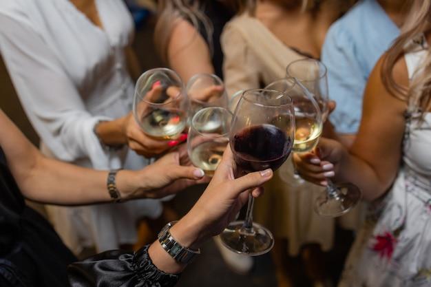 Feier. leute, die gläser weißwein halten und einen toast machen.