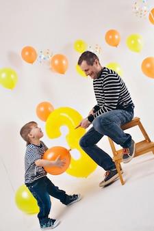 Feier, lustige zeit verbringen - familie auf der party. erwachsene und kinder auf einem weißen hintergrund unter den farbigen kugeln feiern ihren geburtstag