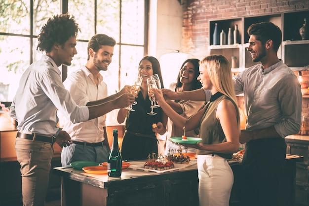 Feier mit engsten freunden. gruppe fröhlicher junger leute, die mit sektflöten jubeln und glücklich aussehen, während sie in der küche feiern?