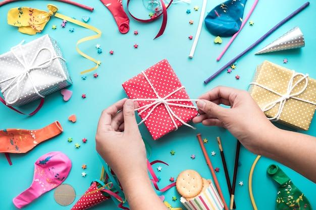 Feier, party mit weiblicher hand, die bunte geschenkbox verziert, die mit element vorhanden ist