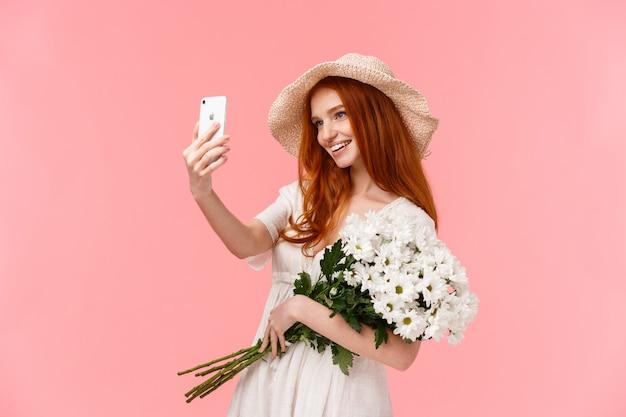 Feier, social media und internet-konzept. anziehende freche rothaarigefrau im strohhut, frühlingskleid, den blumenstrauß halten und nehmen selfie auf dem smartphone mit den weißen blumen und lächeln gefallen