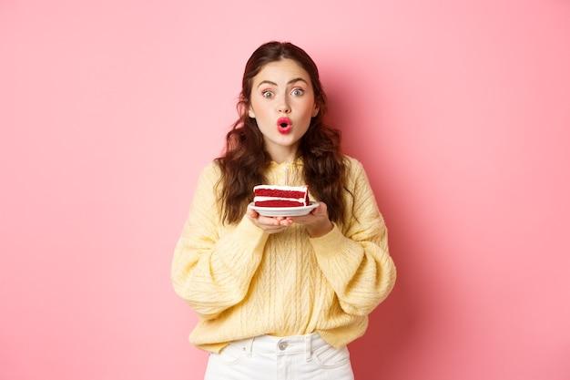 Feier und feiertage. aufgeregtes geburtstagskind, das b-day-kuchen mit kerze hält und überrascht in die kamera schaut, die gegen rosa wand steht.