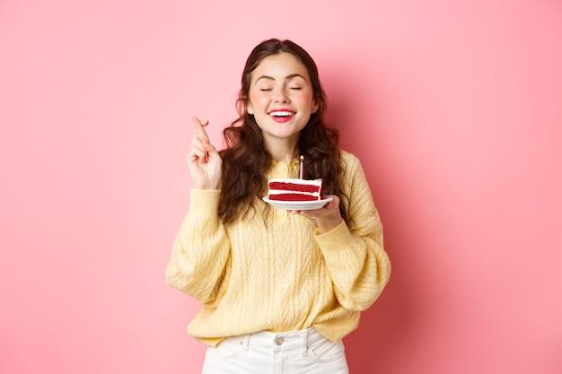 Feier und feiertage. glückliche frau feiert ihren geburtstag, wünscht sich mit geschlossenen augen und gekreuzten fingern, hält bday kuchen mit einer kerze, steht auf rosa wand.