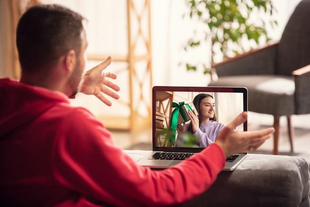 Feier und feiertage während des quarantänekonzepts. freunde oder familie packen geschenke aus, während sie per videoanruf sprechen. sieh glücklich, fröhlich und aufrichtig aus. konzept des neuen jahres, technologien, emotionen.