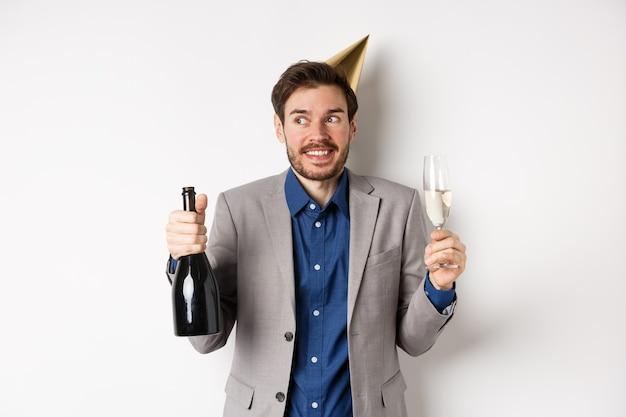Feier- und feiertagskonzept. alles gute zum geburtstag kerl in anzug und partyhut, der champagner trinkt, flasche und glas hält, lächelt und beiseite schaut.