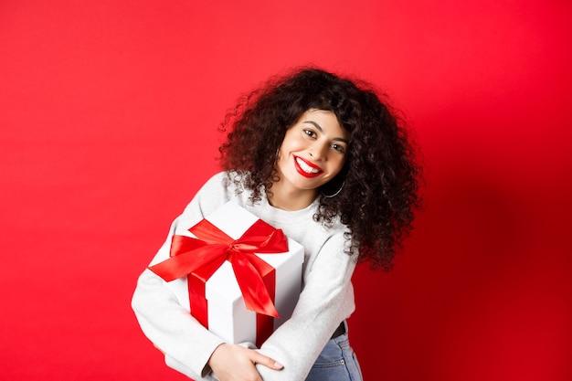 Feier- und feiertagskonzept. glückliche frau, die geburtstagsgeschenk hält und an der kamera lächelt, in der freizeitkleidung stehend, roter hintergrund.
