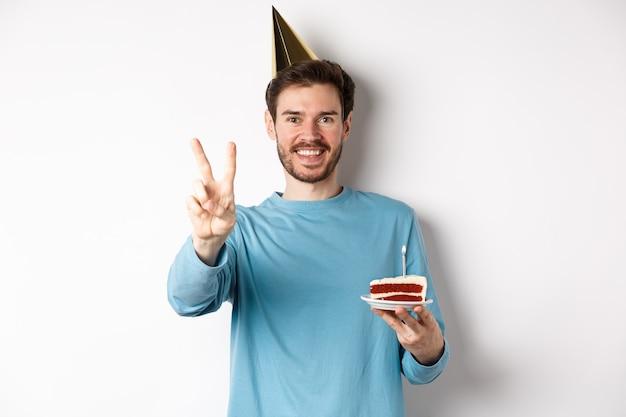 Feier- und feiertagskonzept. glücklicher junger mann, der geburtstag feiert, foto mit friedenszeichen macht, partyhut trägt und bday kuchen, weißen hintergrund hält.