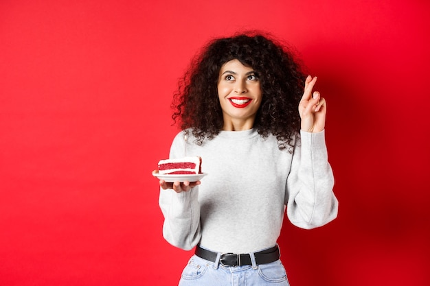 Feier- und feiertagskonzept. hoffnungsvolle junge frau, die geburtstagswunsch macht, die finger gekreuzt hält und nach oben schaut, b-tageskuchen mit kerze, rotem hintergrund haltend.